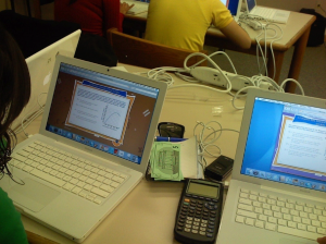 Picture of computers on a desk with a scientific calculator next to them.