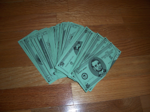 Picture of green play money on a wooden surface.